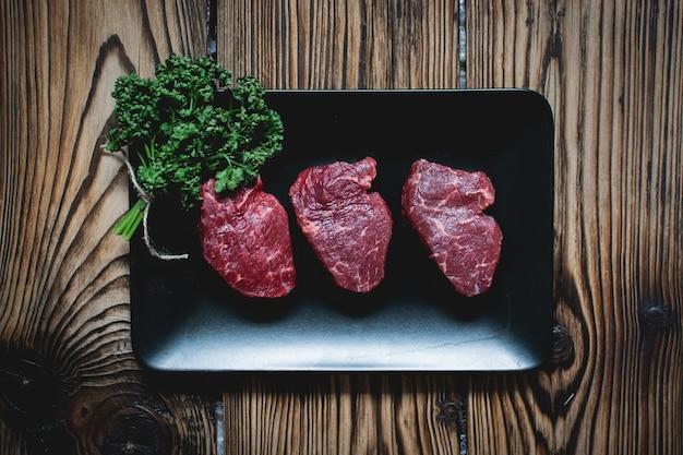 Ruwe rundvleeslapjes vlees op een zwarte plaat