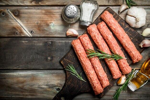 Ruwe rundvleesworstjes met kruiden en specerijen. op een houten achtergrond.