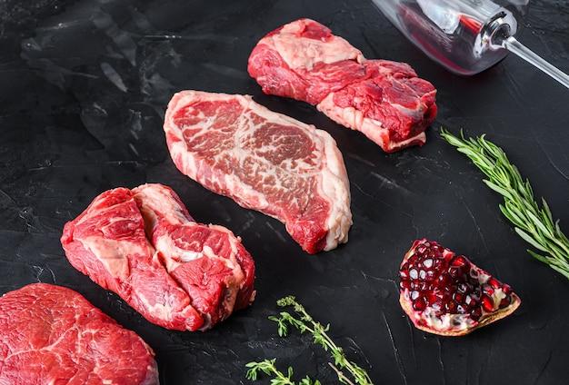 Ruwe set van achterdeel, bovenste mes, biefstuk van het chuck roll biefstuk gesneden, met rozemarijn, knoflook, granaatappel, tomaat, peperkorrels op zwarte getextureerde tafel, zijaanzicht.