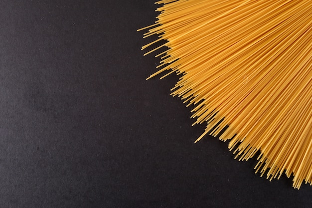 Ruwe spagetti pasta geïsoleerd op zwart oppervlak bovenaanzicht met kopie ruimte