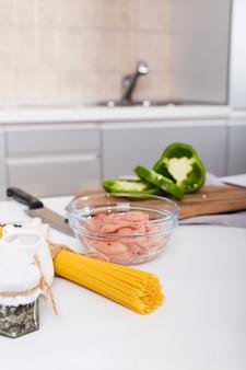 Ruwe spaghetti; kip in kom en gesneden paprika op tafel