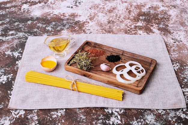 Ruwe spaghetti met verse kruiden op tafellaken.