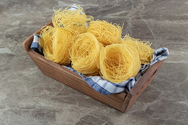 Ruwe spaghetti nesten in houten kist