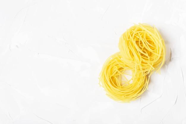 Ruwe spaghetti op de witte steenachtergrond met copyspace