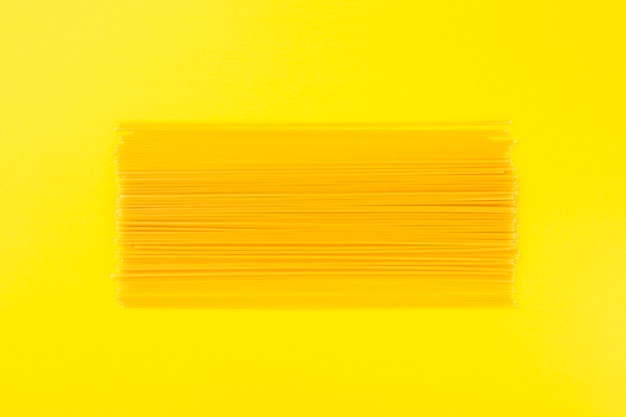 Ruwe spaghetti op gele achtergrond