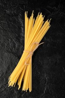 Ruwe spaghetti vastgebonden met touw op zwarte ondergrond