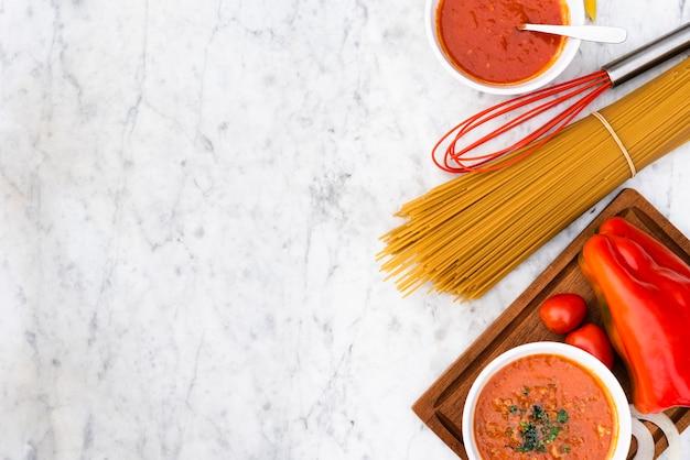 Ruwe spaghettideegwaren en saus met verse tomaten op marmeren geweven achtergrond