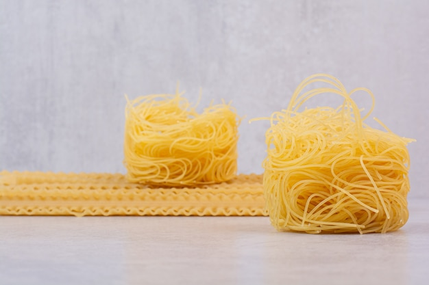 Ruwe spaghettinest en deegwaren op steenoppervlakte