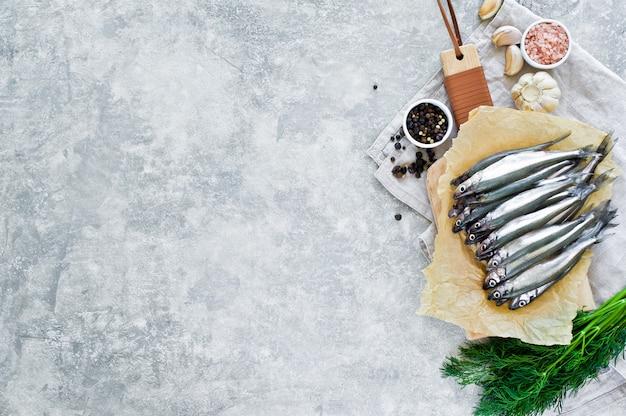 Ruwe spiering op een houten snijplank, dille, roze zout, peper en knoflook.