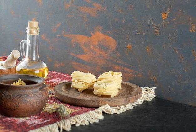 Ruwe spiraalvormige deegwaren in pot met ongekookte fettuccine macaroni