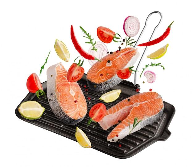 Ruwe steaks van zalm of forelvissen met kruiden en kruiden die op geïsoleerde grillpan vallen