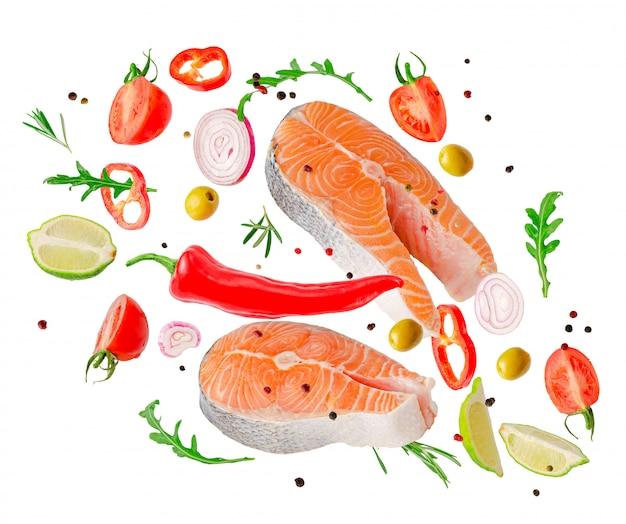 Ruwe steaks van zalmvissen die met geïsoleerde groenten, kruiden en kruiden vliegen
