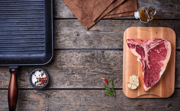 Ruwe t-bone steak en ijzeren grillpan