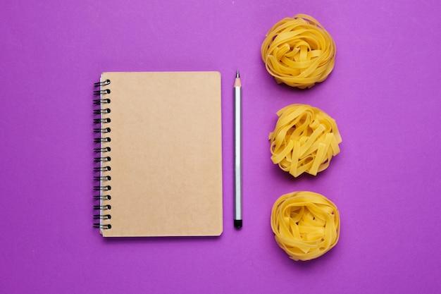 Ruwe tagliatelle-noedel en notitieboekje met potlood
