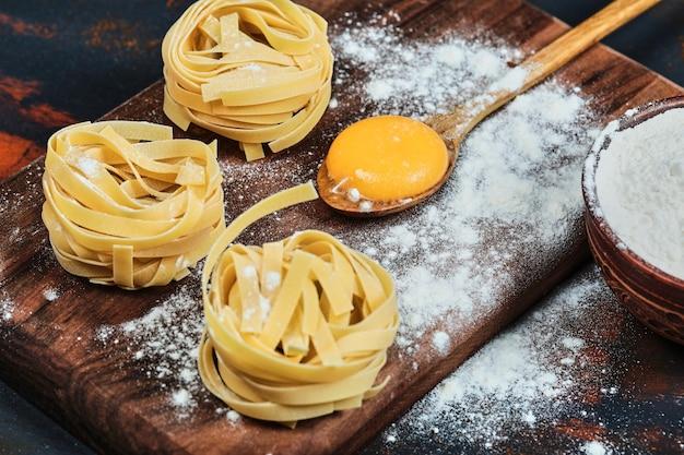 Ruwe tagliatelle pasta op een houten bord met kom poeder.