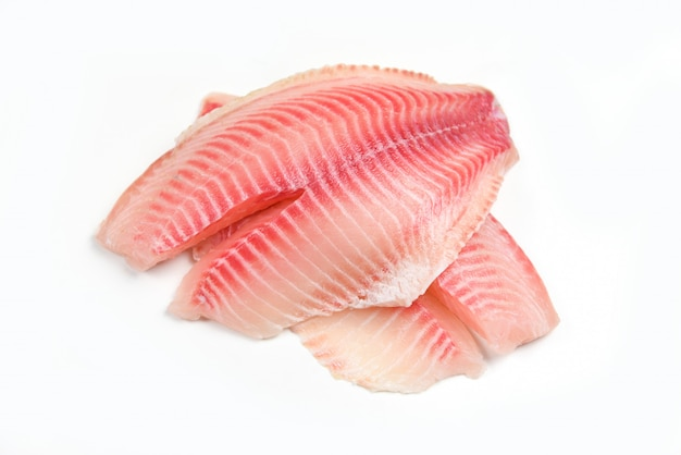 Ruwe tilapia filetvissen die op witte achtergrond voor het koken van voedsel worden geïsoleerd - verse visfilet die voor lapje vlees of salade wordt gesneden