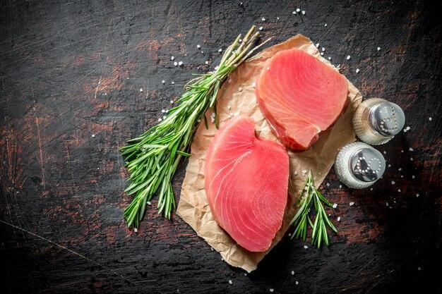 Ruwe tonijnfilet op papier met rozemarijn en kruiden op donkere rustieke tafel.