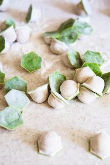 Ruwe tweekleurige witte en groene dumplings met spinazie, kaas of vlees op een tafel met bloem
