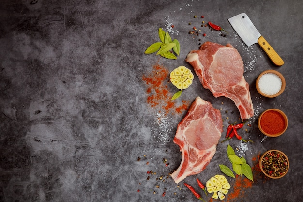 Ruwe varkenskarbonades met kruiden en hakmes op donkere achtergrond. bovenaanzicht.