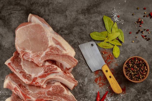 Ruwe varkenskarbonades met kruiden en hakmes op donkere ondergrond