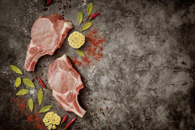 Ruwe varkenskarbonades met kruiden op donkere achtergrond. bovenaanzicht.