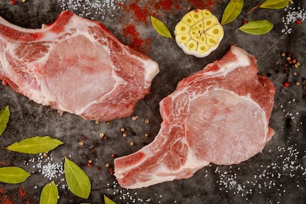 Ruwe varkenskarbonadesrib met kruiden op grijze oppervlakte