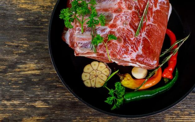 Ruwe varkenskotelet met kruiden en rode spaanse peperpeper.