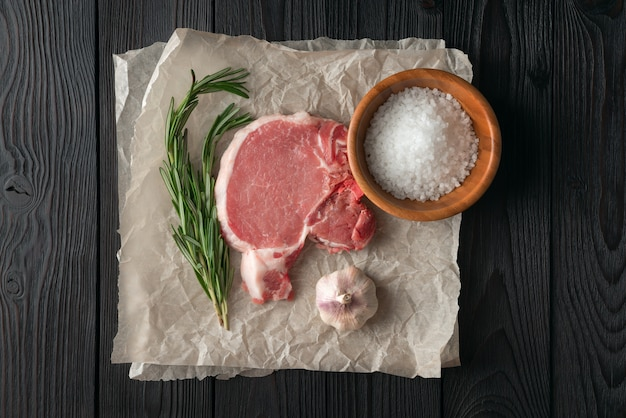 Ruwe varkenskotelet met kruiden voor grill of het koken op houten achtergrond