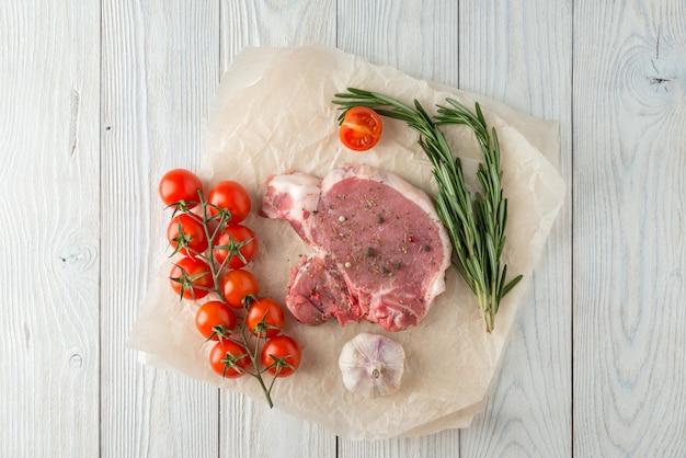 Ruwe varkenskotelet met kruiden voor grill of het koken op houten
