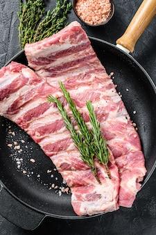 Ruwe varkensribbetjes met specerijen en kruiden in een pan.