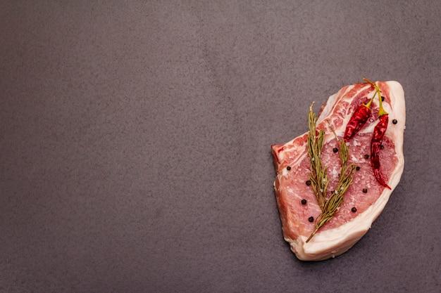 Ruwe varkensvleeslapje vlees op grijze lijst