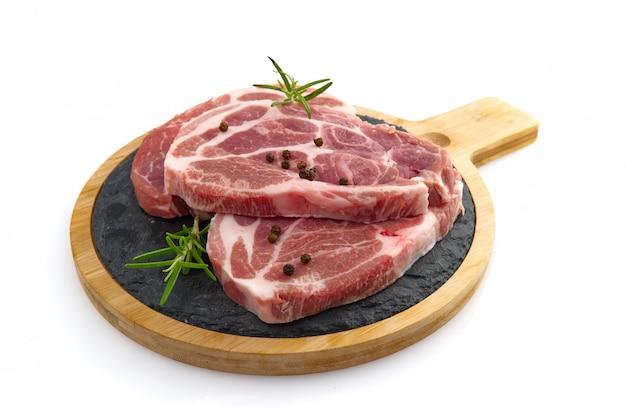 Ruwe varkensvleesplakken op zwarte steenplaat, die op wit wordt geïsoleerd.