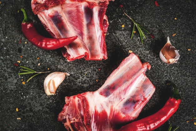 Ruwe vers vlees, ongekookte lam of rundvleesribben met hete peper, knoflook en kruiden op donkere steen, copyspace hoogste mening