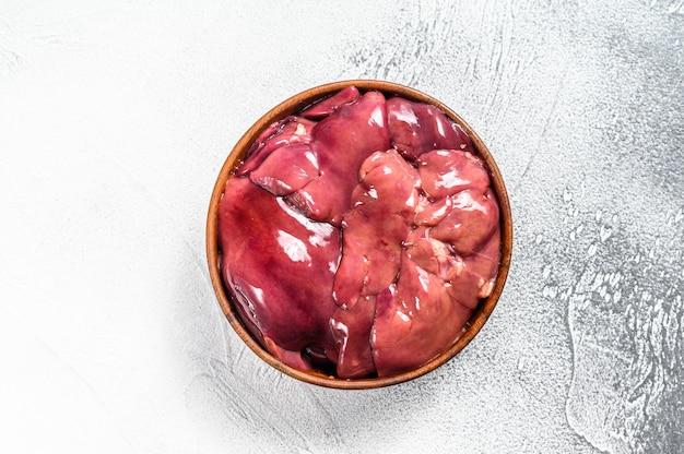 Ruwe verse kalkoenlever in een kom op wit. bovenaanzicht. kopieer ruimte