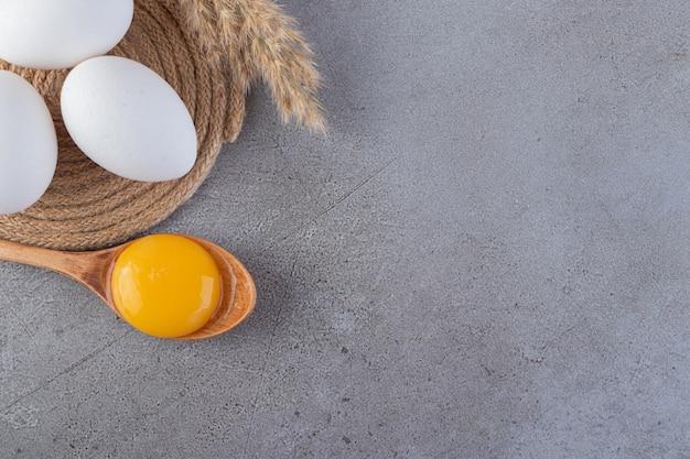 Ruwe verse witte kippeneieren die op een steenachtergrond worden geplaatst.