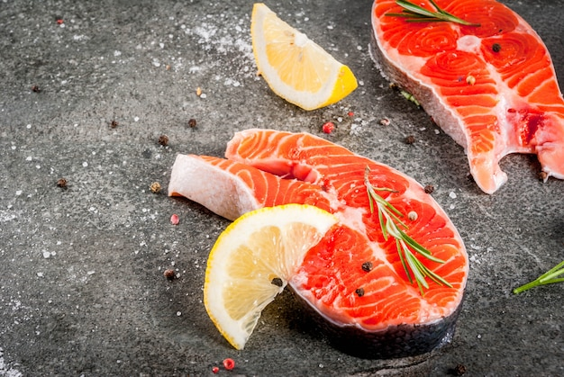 Ruwe verse zalmvissen met ingrediënten voor het koken van olijfolie, citroen, ui, peterselie, rozemarijn, op zwarte steenlijst, copyspace