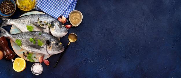 Ruwe vissen met het koken van ingrediënten op donkerblauwe achtergrond