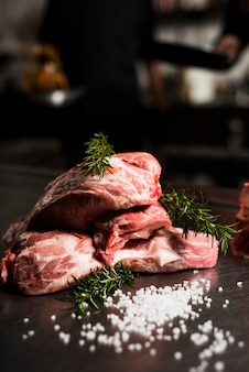 Ruwe vleeslapjes vlees met rozemarijn op lijst