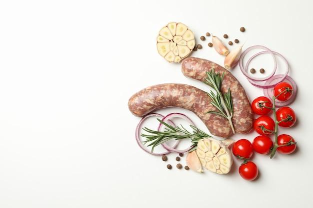 Ruwe worsten, kruiden en specerijen op witte lijst