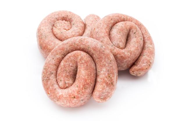 Ruwe worsten met kruiden en specerijen die op wit worden geïsoleerd