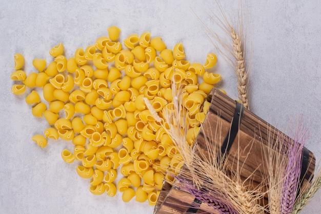 Ruwe zeeschelpvormige pasta op wit oppervlak met houten emmer