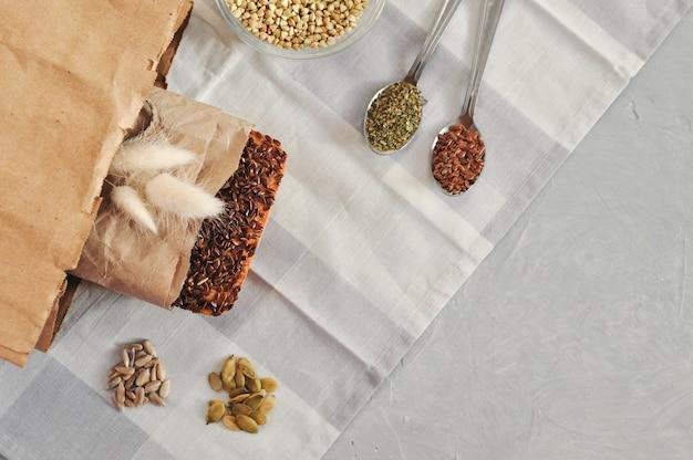 Ruwe zelfgemaakte vegan zuurdesembrood gemaakt van groene boekweit met lijnzaad, zonnebloem, pompoen in een papieren kraft tas. gezonde en goede voeding
