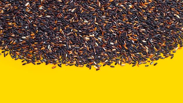 Ruwe zwarte kleverige rijst op gele achtergrond.