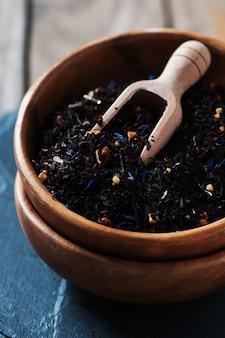 Ruwe zwarte thee op de houten tafel