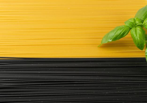 Ruwe zwarte zelfgemaakte spaghetti op donkere achtergrond. de droge zwarte en gele textuur van eiernoedels