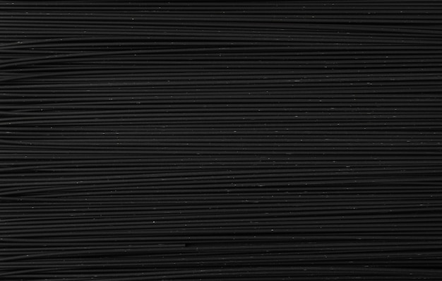 Ruwe zwarte zelfgemaakte spaghetti op donkere achtergrond. droge zwarte noedels textuur