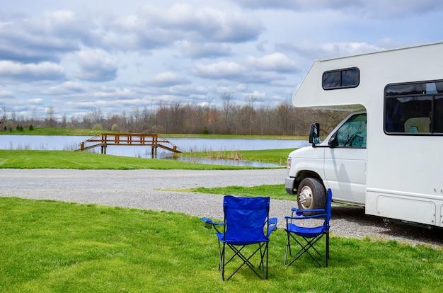 Rv (camper) en stoelen op de camping, gezinsvakantie, vakantiereis in camper