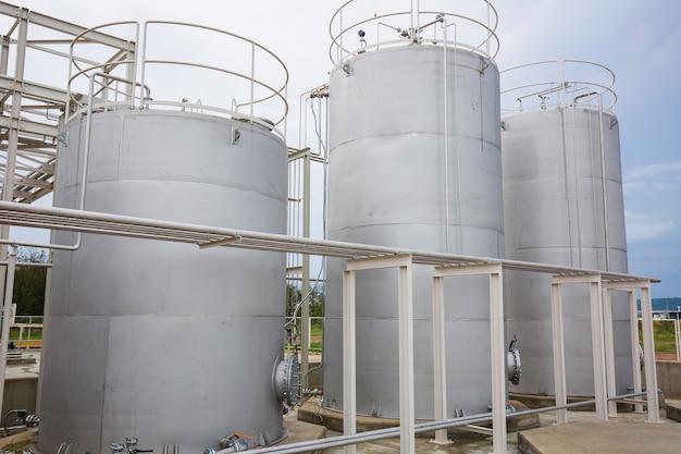 Rvs silo's in de chemische industrie, bulk kunststof silo tegen een blauwe lucht