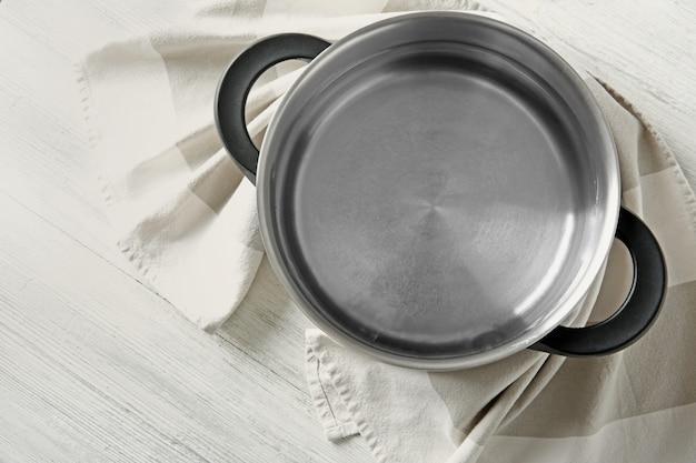 Rvs steelpan en servet op witte houten tafel