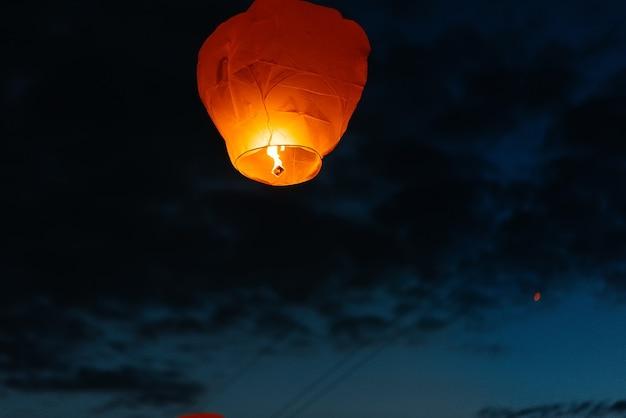 's avonds, bij zonsondergang, lanceren mensen met hun familieleden en vrienden traditionele lantaarns. traditie en reizen.